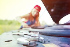 Wait for roadside assistance. Blured portrait of a young woman standing next to her car trying to fix the engine stock photography