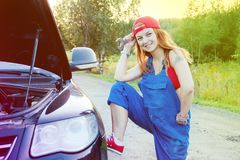 Wait for roadside assistance. Portrait of a young woman standing next to her car and open car hood royalty free stock images