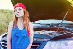 Wait for roadside assistance. Portrait of a young woman standing next to her car and open car hood stock photo