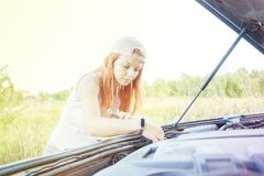 Wait for roadside assistance. Portrait of a young woman standing next to her car trying to fix the engine royalty free stock photos