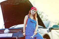 Wait for roadside assistance. Portrait of a young woman standing next to her car with wrenches and open car hood stock photos
