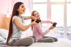Enigmatical teenager playing with her sister at home stock photography