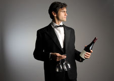 Waiter. Handsome Waiter with a bottle of wine and glasses Stock Photos