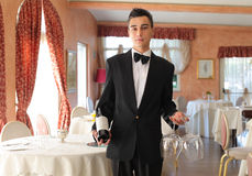 Waiter. Young waiter holding a bottle of wine and wine glasses in a luxury restaurant stock photo