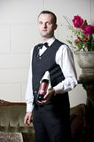 Waiter. Elegantly dressed waiter presenting a bottle of expensive wine in a vintage interior of a restaurant Royalty Free Stock Image