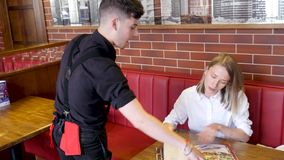 The waiter advising different dishes for demanding and emotional girl in the restaurant
