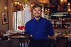 Waiter with alcoholic cocktail for customer. Royalty Free Stock Images
