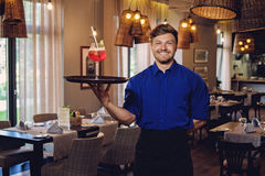 Waiter with alcoholic cocktail for customer. Royalty Free Stock Photography