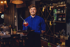 Waiter with alcoholic cocktail for customer. Waiter with alcoholic cocktail for customer Stock Images