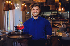 Waiter with alcoholic cocktail for customer. Stock Images