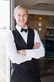 Waiter with arms crossed in restaurant Stock Images
