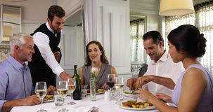 Waiter attending to a table of happy friends stock video footage