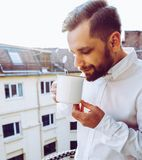 Waiter in a balcony taking a mug of coffee. Handsome turkish guy with brown bear. Waiter in a balcony taking a mug of coffee.Handsome turkish guy with brown bear royalty free stock photos
