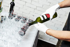 Waiter bartender pouring wine at party. Waiter bartender pouring red wine into glasses at party event Royalty Free Stock Image