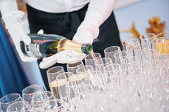 Waiter bartender pouring wine at party. Waiter bartender pouring red wine into glasses at party event Royalty Free Stock Photo