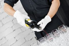 Waiter bartender pouring wine at party. Waiter bartender pouring white wine into glasses at party event Royalty Free Stock Images