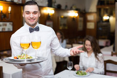Waiter with beverages. Positive waiter holding tray with glasses of wine in bar Royalty Free Stock Photo