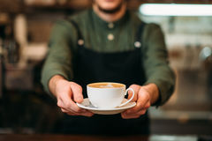 Waiter in black apron stretches a cup of coffee Royalty Free Stock Images
