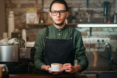 Waiter in black apron stretches a cup of coffee Royalty Free Stock Photos