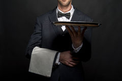 Waiter in black suit holding tray over black background. Royalty Free Stock Image