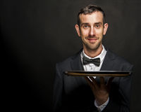 Waiter in black suit holding tray over black background. Butler Stock Photos