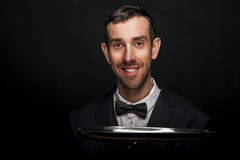 Waiter in black suit holding tray over black background. Smiling Stock Photos