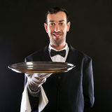 Waiter in black suit holding tray over black background. Royalty Free Stock Images