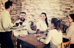 Waiter bringing order to visitors. Cheerful male waiter bringing order to visitors in country restaurant Royalty Free Stock Image