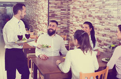 Waiter bringing order to visitors. Positive male waiter bringing order to visitors in country restaurant Royalty Free Stock Photo