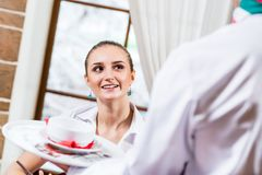 Waiter brings a dish for a nice woman Stock Images