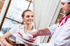 Waiter brings a dish for a nice woman Stock Image