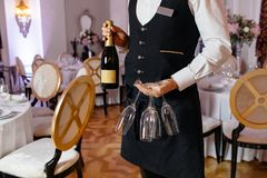 Waitress holding a dish of champagne and wine glasses at some fe Royalty Free Stock Images