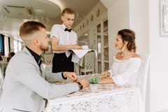 Waiter brought cup of coffee for beautiful couple in a cafe Royalty Free Stock Images