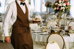 Waiter in the brown outfit serves on the wedding Stock Photography