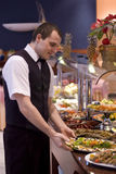Waiter and buffet. A handsome young waiter presents an impressive buffet in a hotel Royalty Free Stock Photo