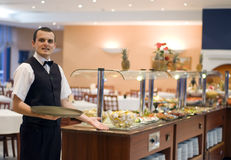 Waiter and buffet. A handsome young waiter presents an impressive buffet in a hotel Royalty Free Stock Photography