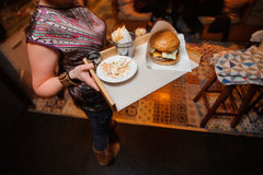 Waiter with burger on plate Stock Photography