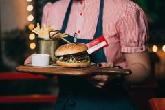 The waiter carries a burger. stock image