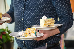 Waiter carries plates with desserts of cakes. On some festive event, party or wedding reception stock image