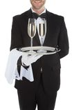 Waiter Carrying Champagne Flutes On Tray. Midsection of waiter carrying champagne flutes on tray over white background Royalty Free Stock Photos