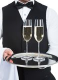 Waiter Carrying Champagne Flutes On Tray. Midsection of waiter carrying champagne flutes on tray over white background Stock Photo