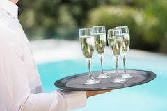 Waiter carrying champagne flutes on tray. Midsection of waiter carrying champagne flutes on tray at poolside Stock Photos