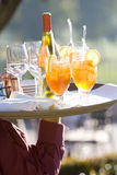Waiter carrying cocktails and wine on tray, outdoors, close-up, rear view, mid-section, focus on foreground Royalty Free Stock Images