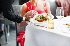 Waiter carrying a plate with salad dish on a wedding. Stock Image