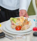 Waiter carrying plates with appetizers. On some festive event Royalty Free Stock Images