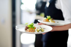 Waiter carrying plates with meat dish Royalty Free Stock Photo