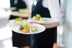 Waiter carrying plates with meat dish Stock Photos