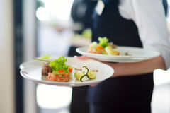Waiter carrying plates with meat dish on some festive event. Party or wedding reception Royalty Free Stock Photography