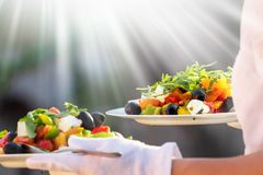 Waiter, carrying three plates with a rich salad at syny day royalty free stock photo