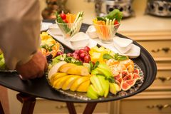 Waiter carrying tray with plates with fruits and vegetables on some festive event Stock Image